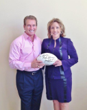 Joe Theismann presenting Linda Shaffer-Vanaria with an autographed football